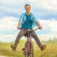 The happy man ride a bicycle in a field